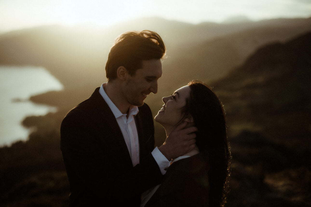 a bride and groom eloping to Scotland mountains and standing in the sun set