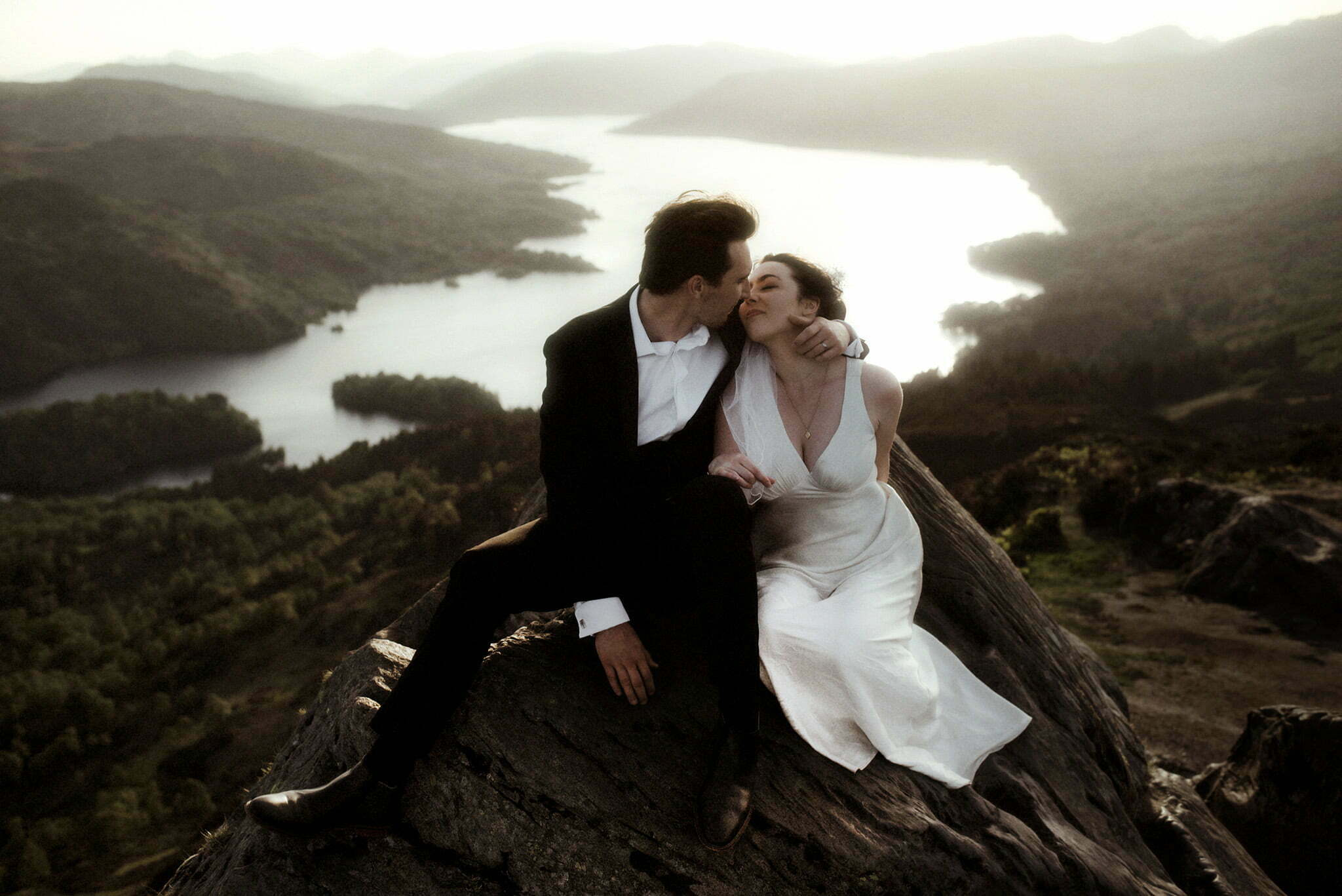 a couple eloping in Scotland sitting on the top of a mountain at sunset