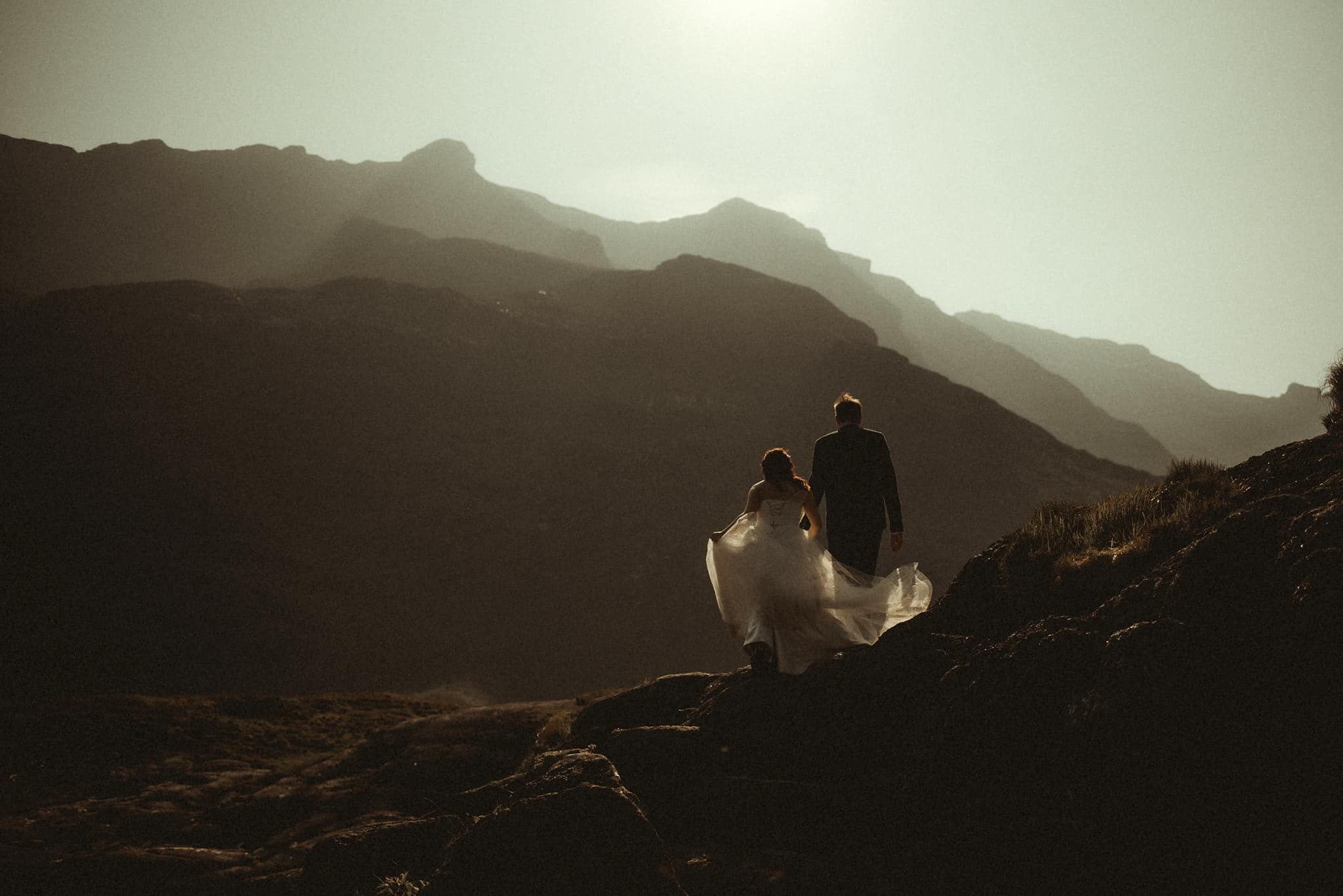 bride and groom walking into the sunset on isle of skye