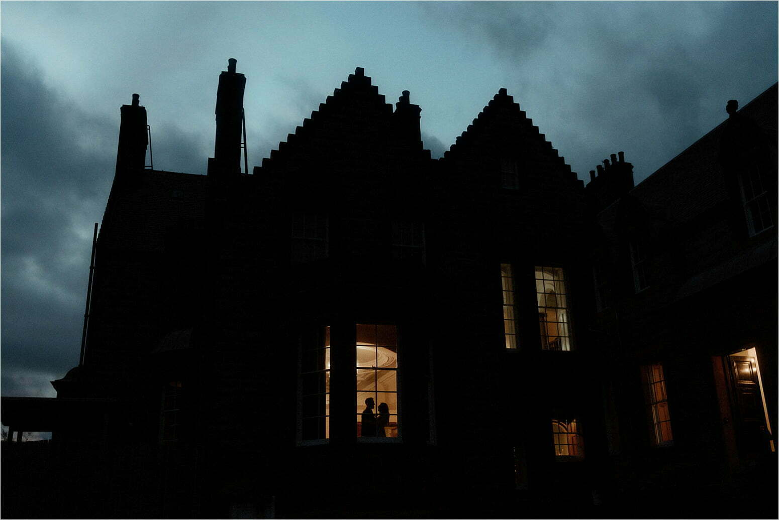 glencoe house at night lit up wit bride and groom in window