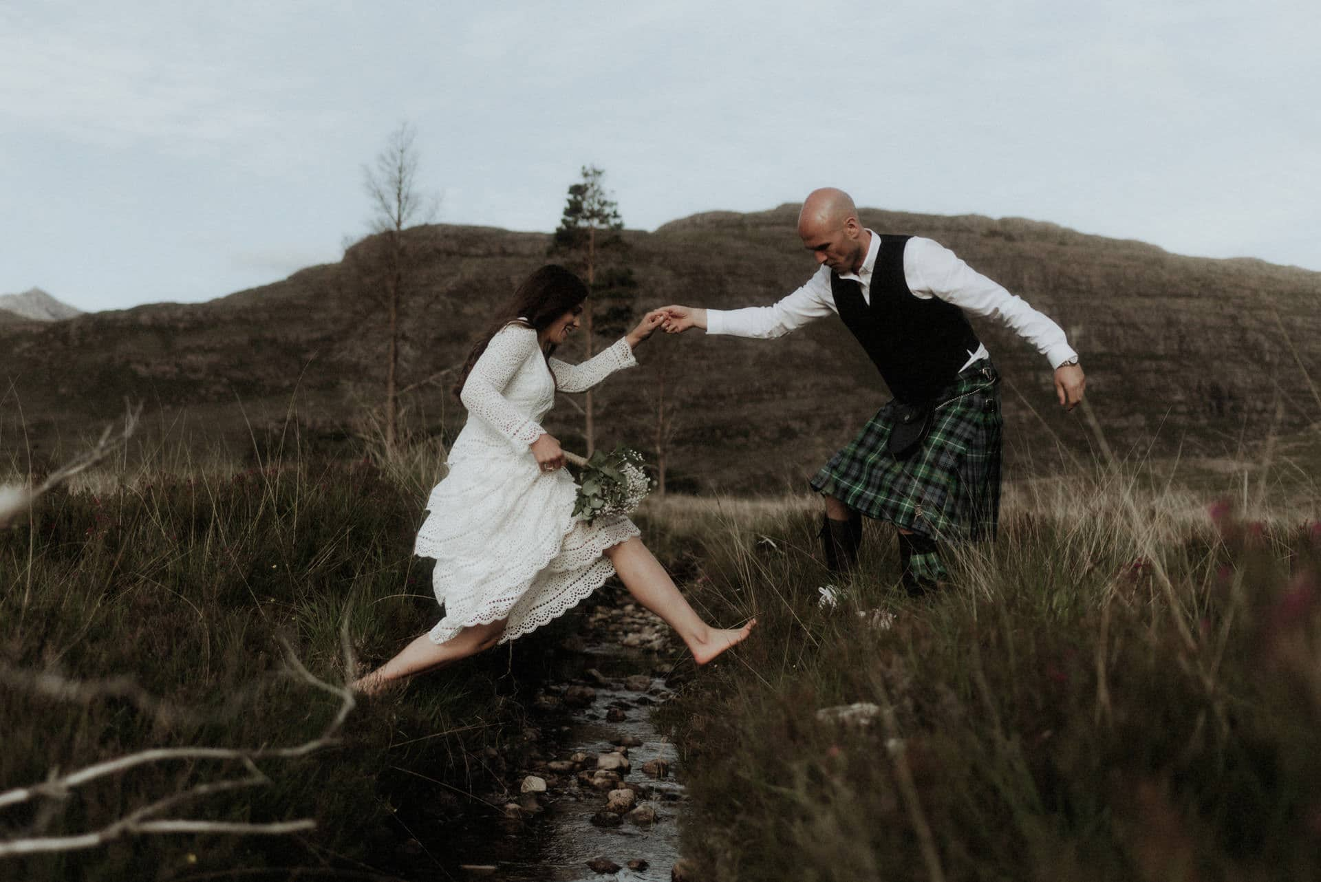 Couple jumping a stream during their elope in scotland
