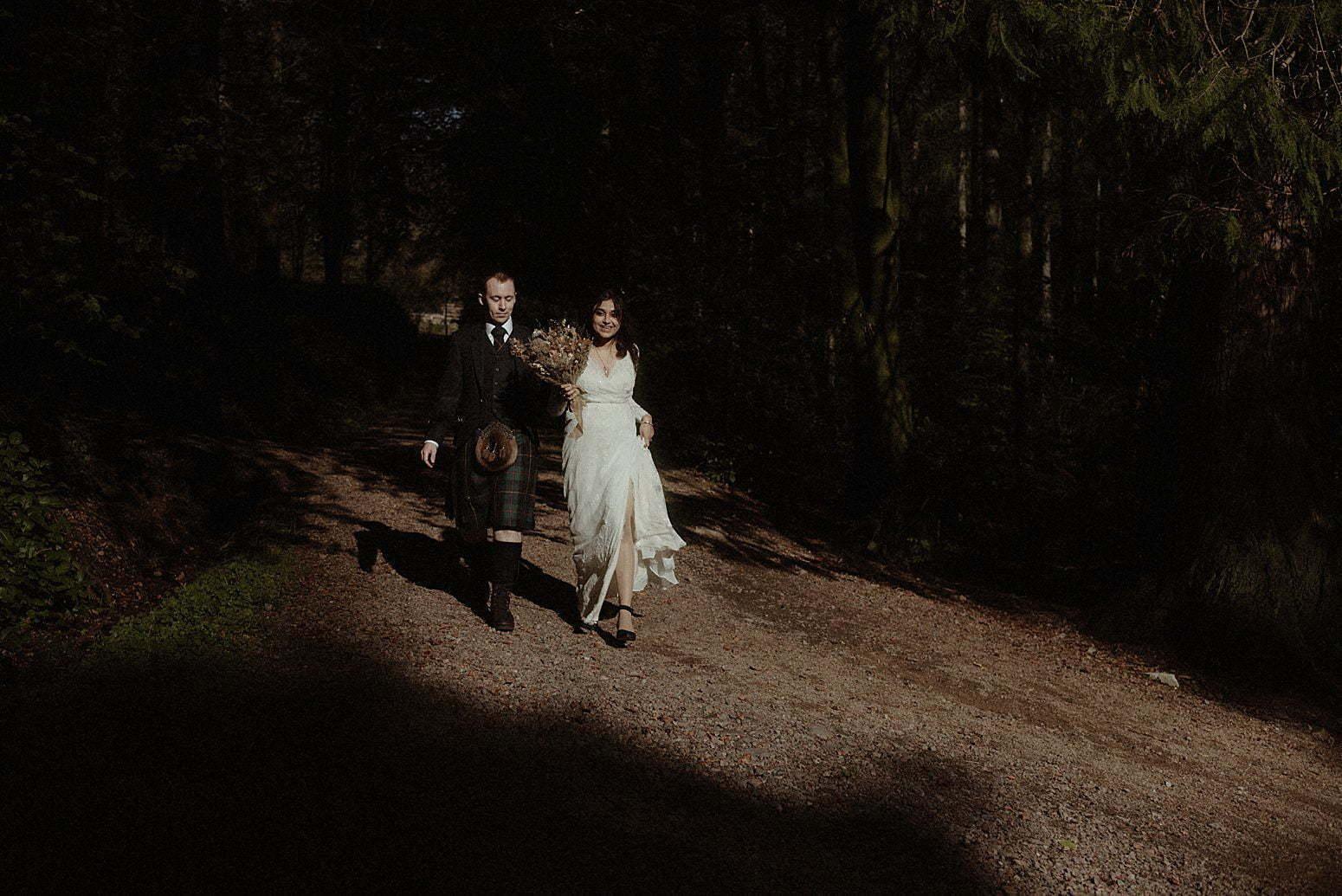 autumn elopement in scotland couple walking into the woodland of glencoe
