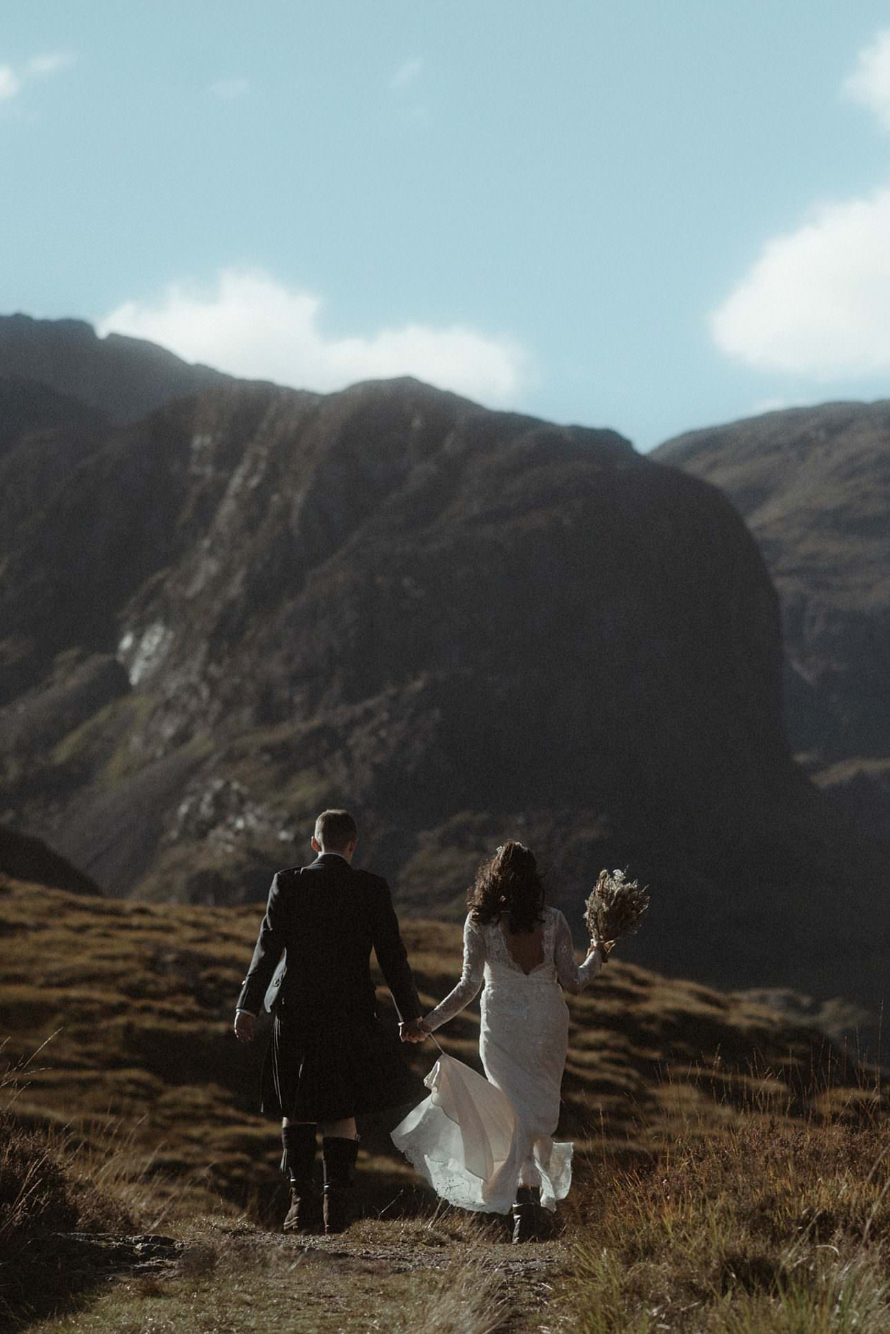 A couple walking in the mountains of glencoe during their elopement