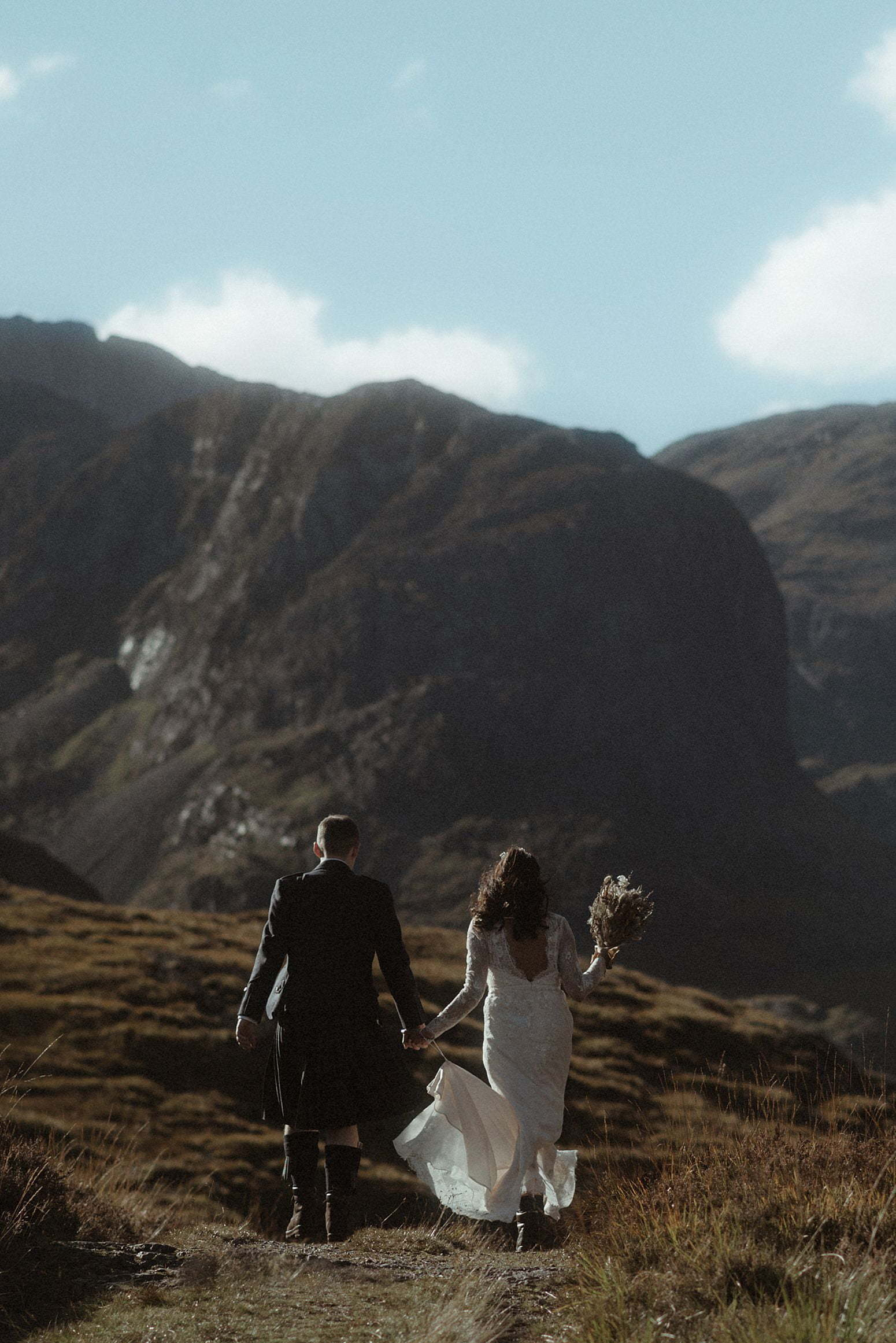elope scotland couple walking into the distance with mountains in front near glencoe