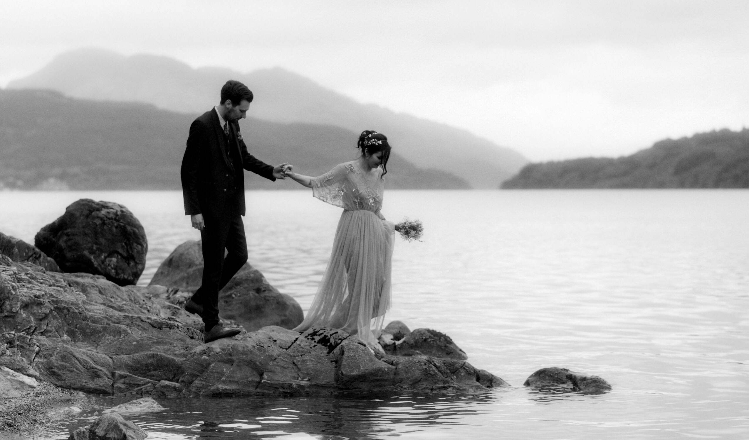 a couple walking next to the beautiful loch lomond having just eloped to scotland