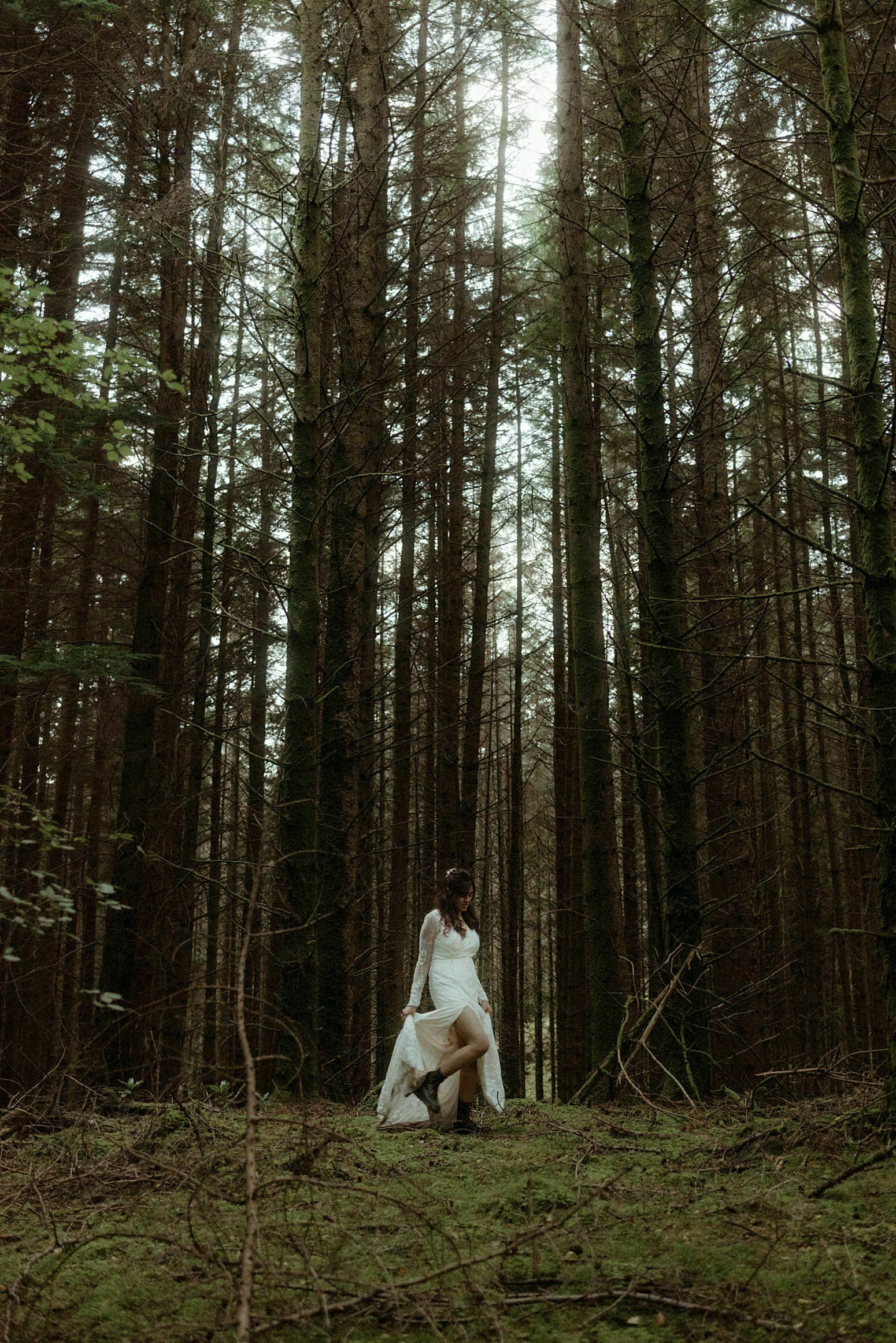 beautiful Bride walking in Woodland in Glencoe after her Scottish elopement