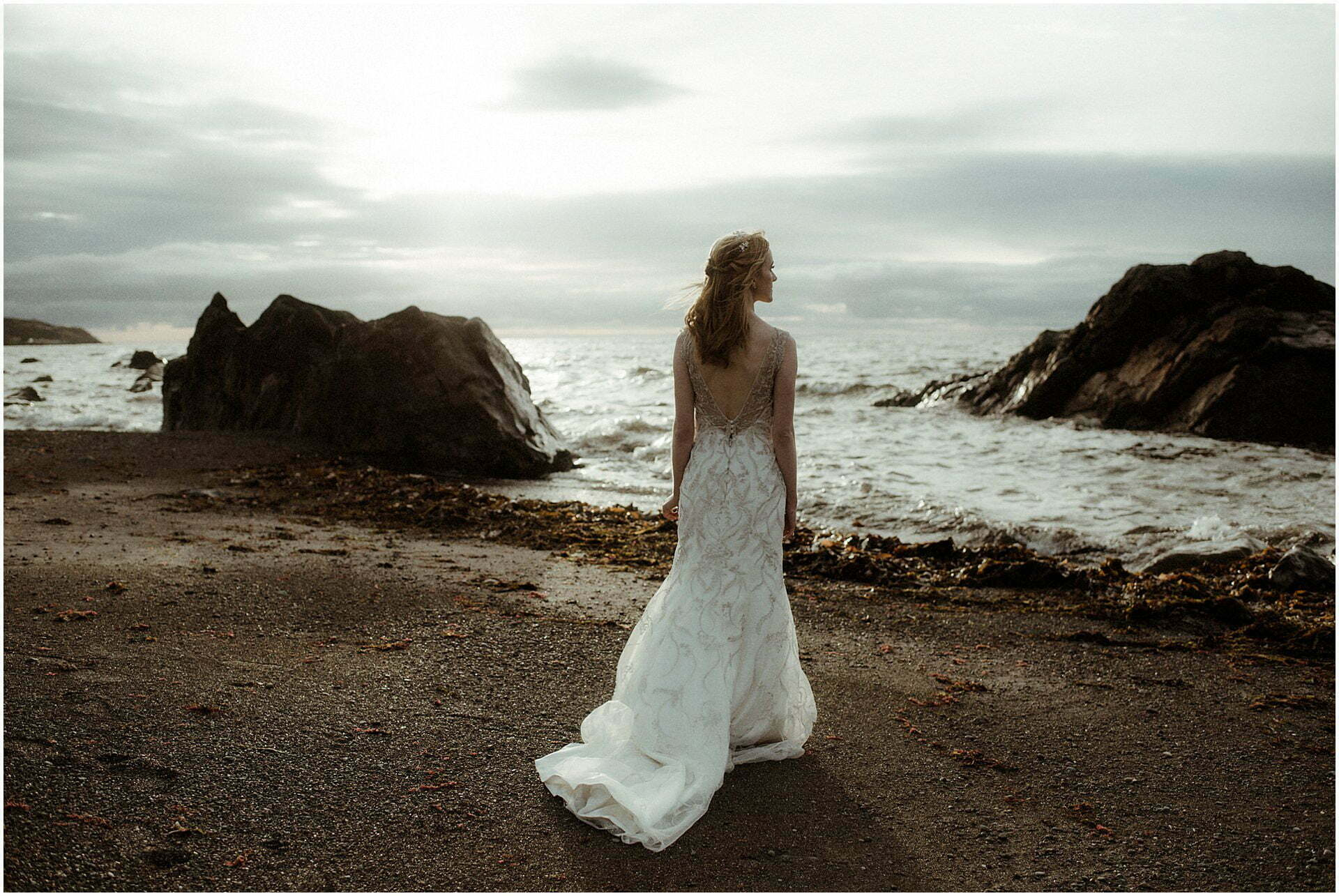 bride standing on a beach in Scotland during a Scottish elopement