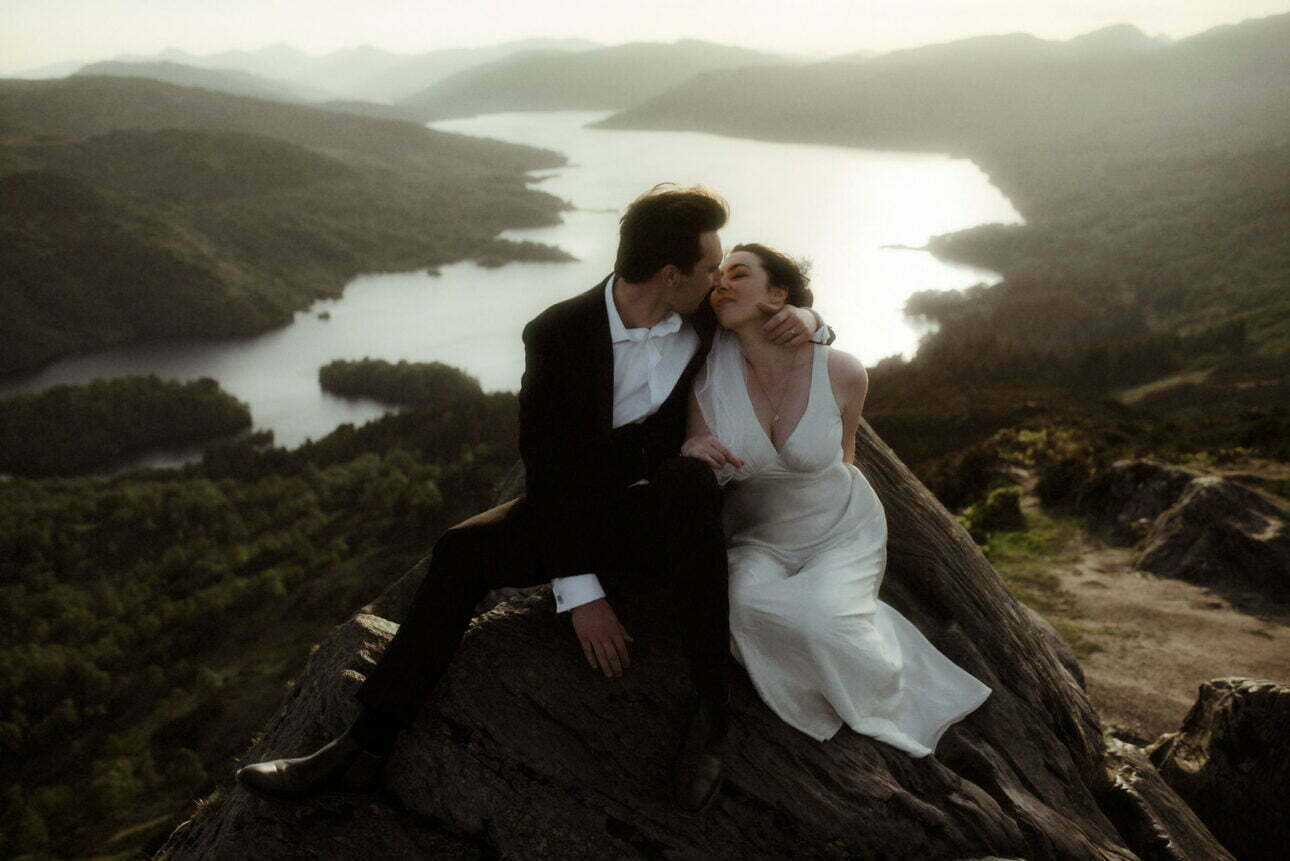 couple sitting on a mountain in Scotland during their elopement