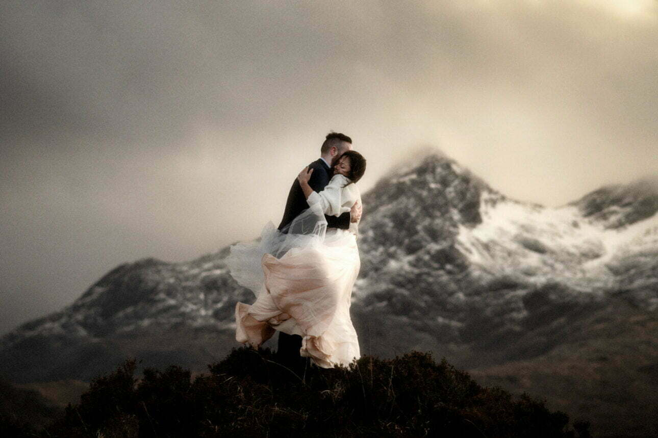 elope to skye couple standing near the cuillin mountains on skye at sunset