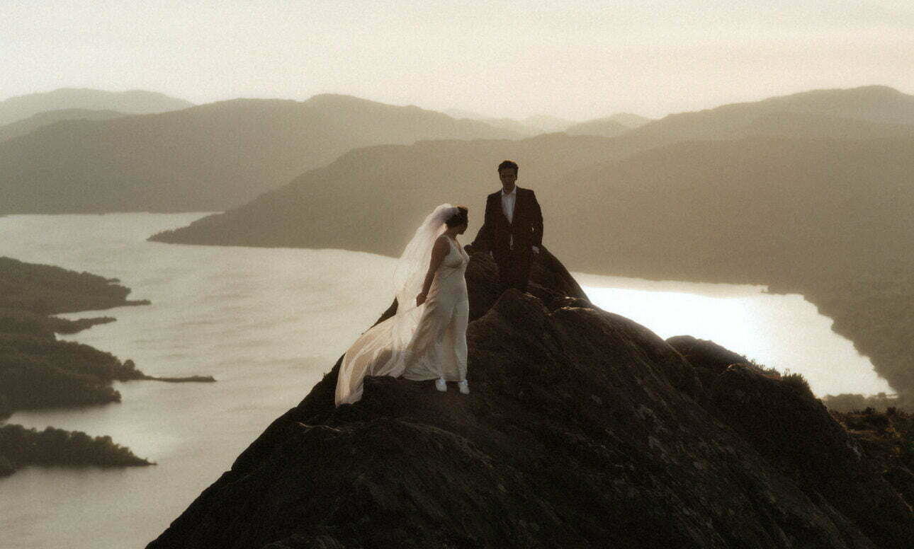 eloping in Scotland Guide with a couple walking in the sun set on top of a mountain