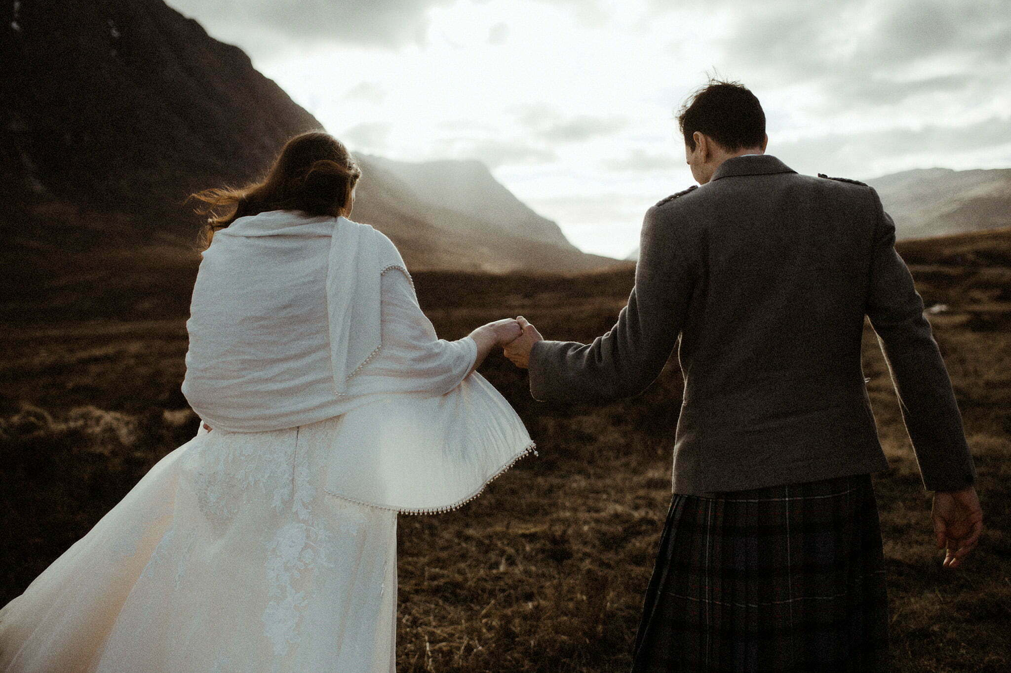 couple walking into the sunlight during their elopement in Glencoe