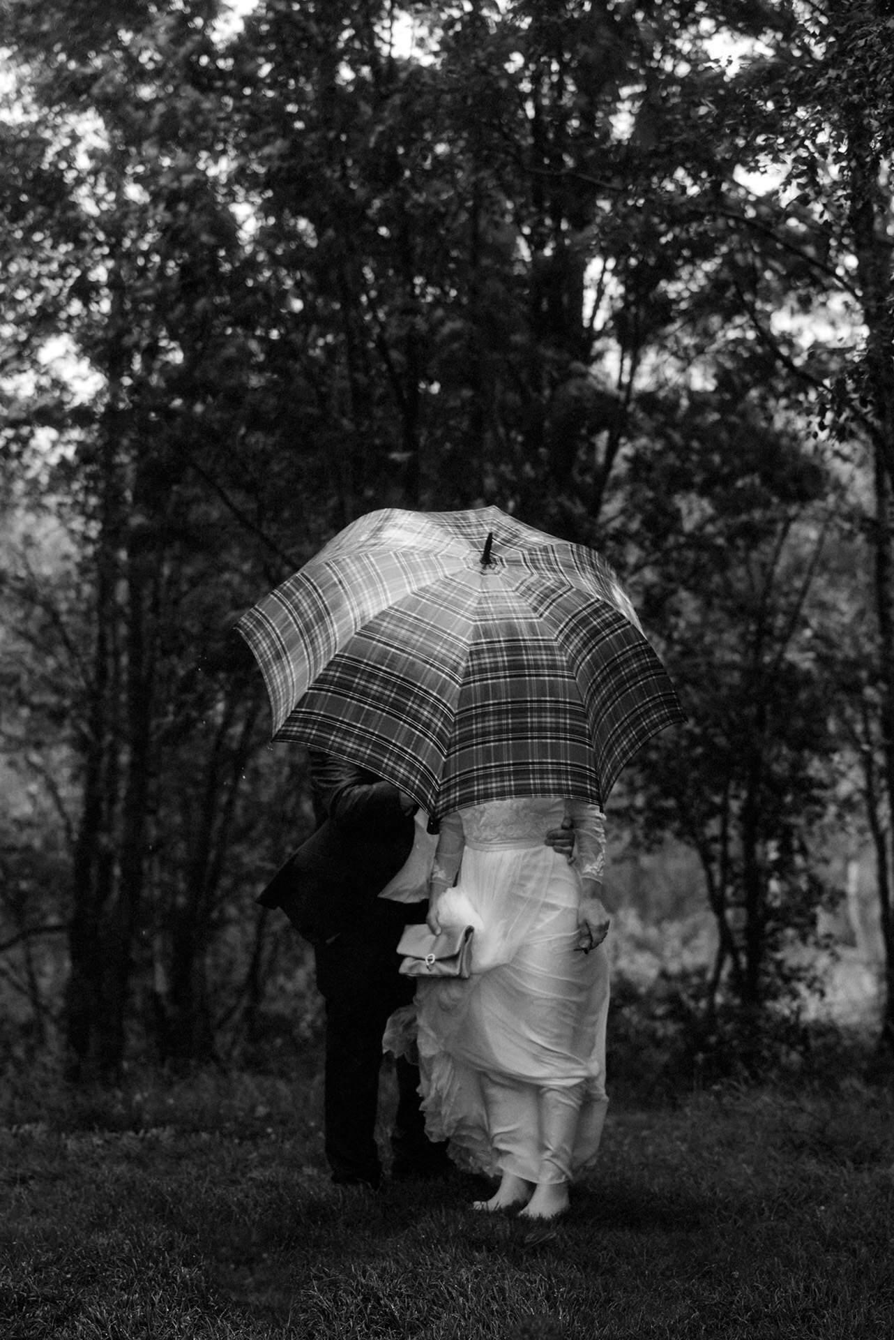 eloping to scotland during wet season couple standing under an umbrella wedding
